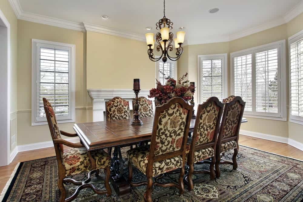 The intricate patterns of the wrought iron chandelier hanging over the wooden rectangular dining table matches with the patterns of the sit cushions and the patterned area rug covering most of the hardwood flooring that contrasts the yellow walls.