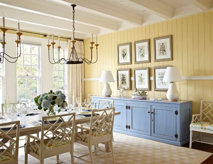 The shiplap yellow walls match the finish of the gray wooden dining room cabinet by the head of the beige wooden table and its beige wooden chairs with lovely designs on its backs that are matching the area rug yellow patterns.