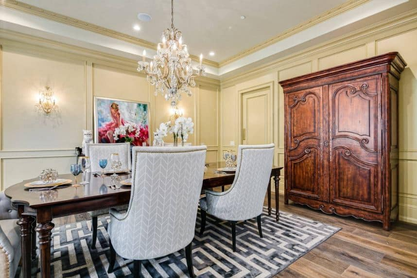 There is a large wooden French cabinet by the head of the wooden elegant dining table that is illuminated by the majestic white crystal chandelier. This matches with the two wall-mounted lamps flanking the colorful painting adorning the yellow wall.
