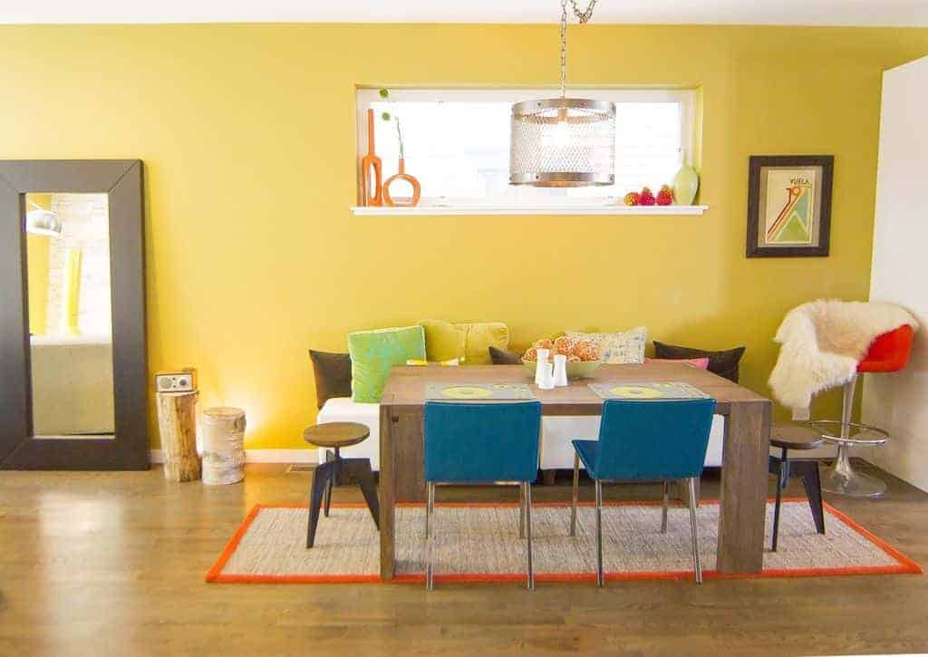 This informal and quirky dining room has colorful throw pillows on a white bench and chairs surrounding the wooden dining table that matches with the hardwood flooring that is topped with an orange area rug.