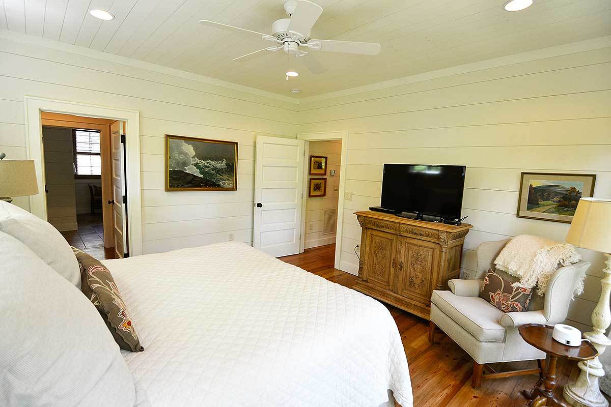The gorgeous shiplap walls of this bedroom matches well with the sheets and pillows of the bed. These are then complemented by the hardwood flooring and the dresser at the foot og the bed with a sitting area beside it.