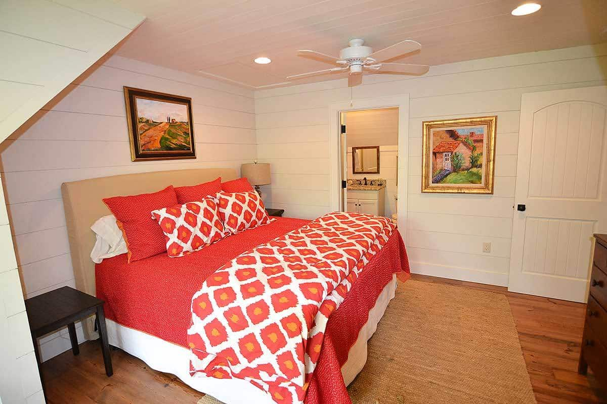 The beige elements in this bedroom are augmented by the charming colorful wall-mounted paintings and the bright red hue of the sheets and pillows of the bed.