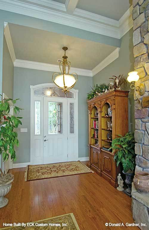 This is a Rustic foyer with a large wooden cabinet, potted plants and a large stone mosaic fireplace.