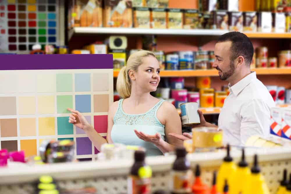 Woman buying paint in a paint store