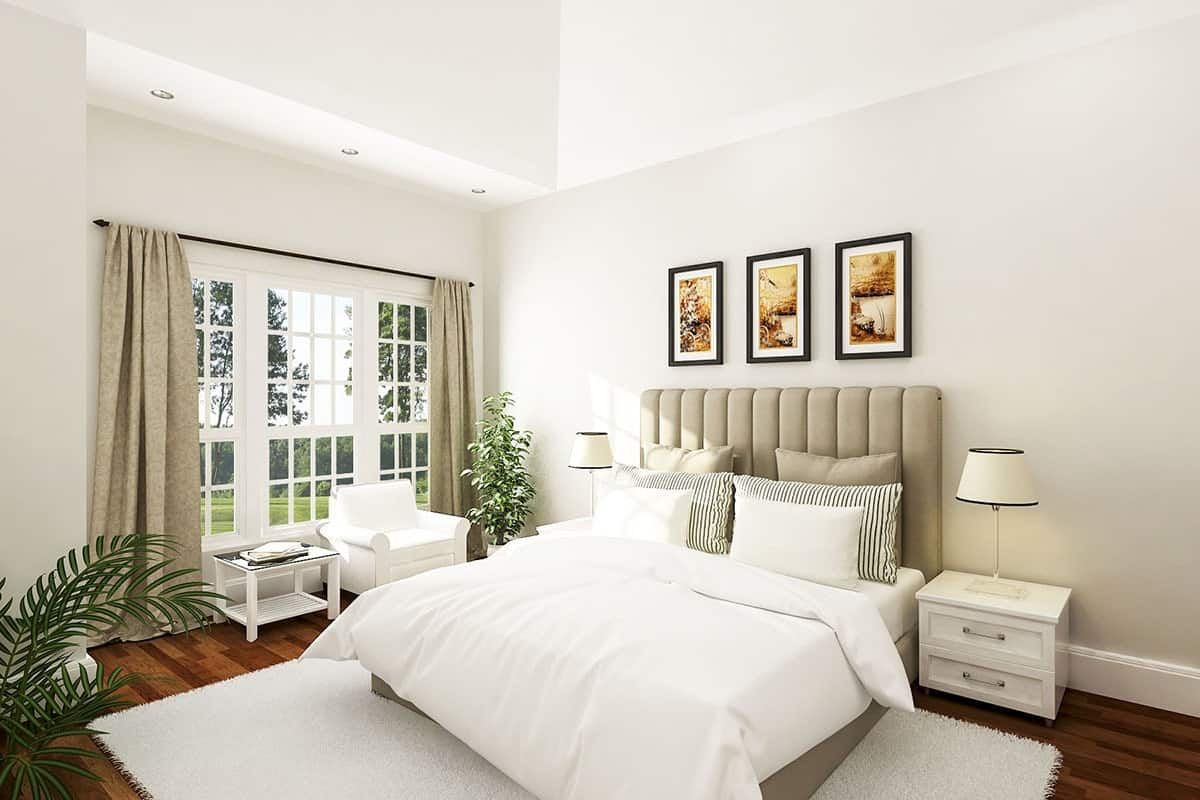 The bright primary bedroom is complemented by the gray cushioned headboard of the bed and the three wall artworks above it. The natural lighting that comes from the large windows further brightens the tall arched ceiling.