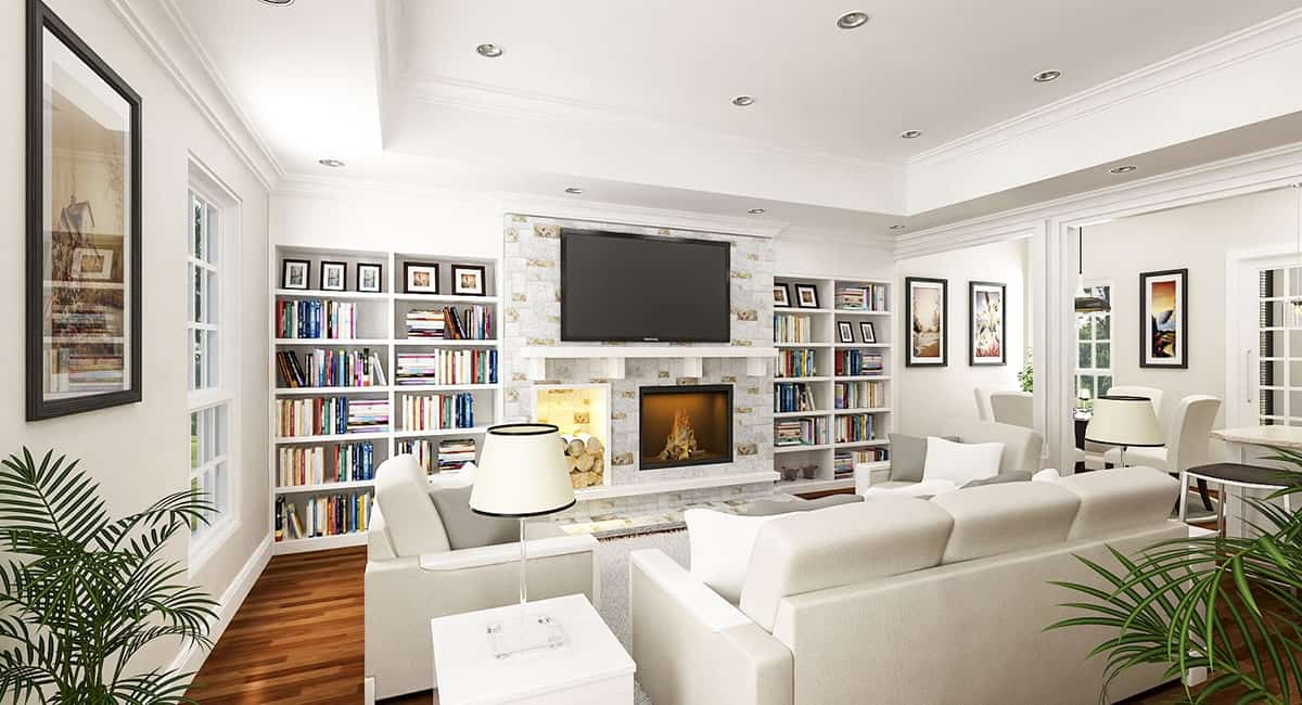 The living room has an elegant tray ceiling and a brick pillar that houses the glass-enclosed fireplace and firewood. This is flanked by embedded shelves and topped with a TV.