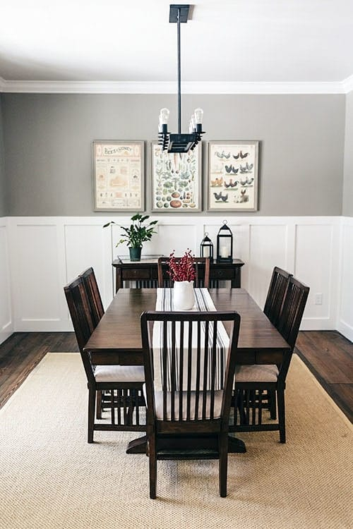 The dark wooden dining table and its surrounding slat-back chairs stand out against the light tones of the white wainscoting and light gray upper walls.