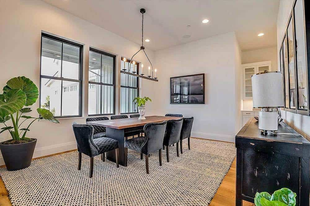 This formal dining room has a homey vibe to its abundance of natural lighting that balances the dark velvet cushioned chairs surrounding the long rectangular wooden dining table.