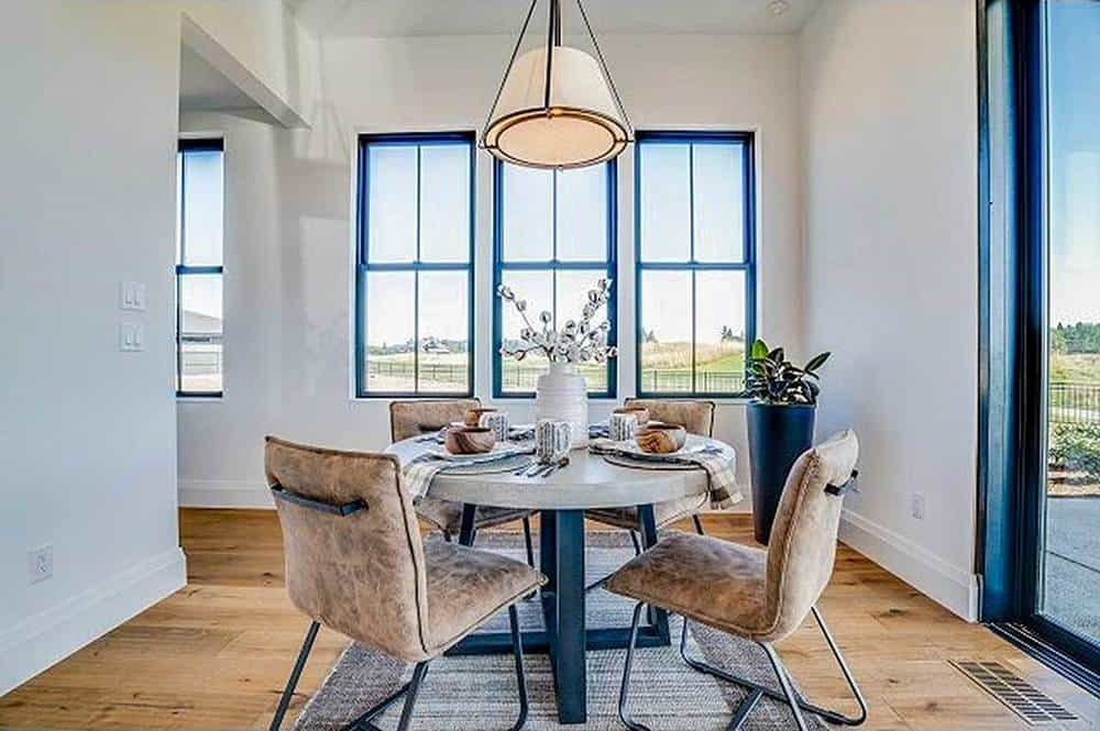 This is an intimate and charming informal dining area with a small white round table surrounded by brown velvet cushioned chairs that match the light hardwood flooring.