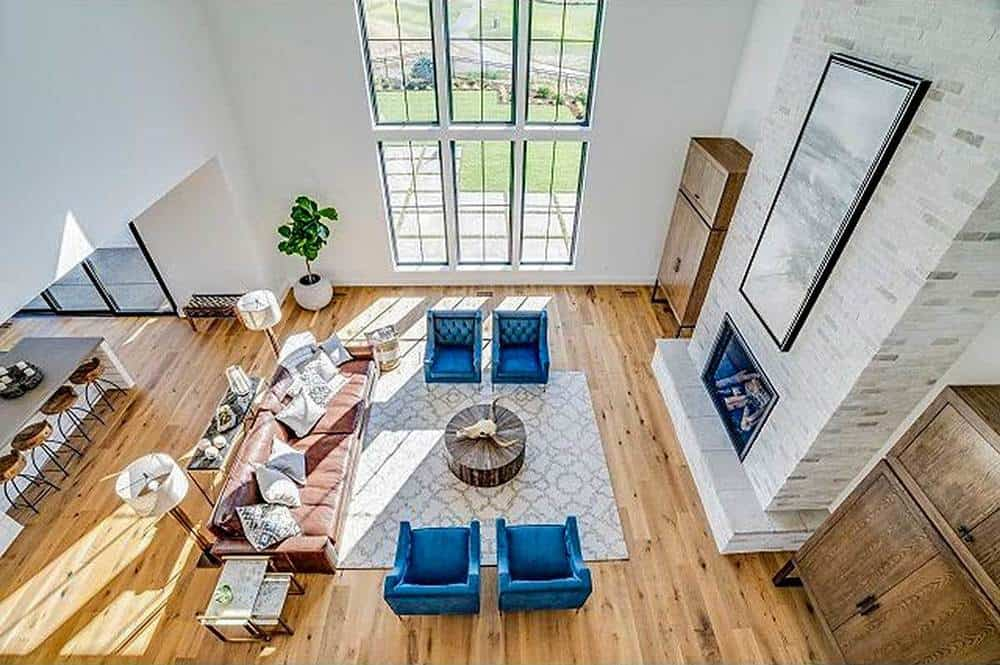 This is a top view of the charming farmhouse-style living room with a tall ceiling paired with a tall glass window. The living room set consists of a brown sofa and two couples of blue arm chairs surrounding a wooden coffee table across from the fireplace.