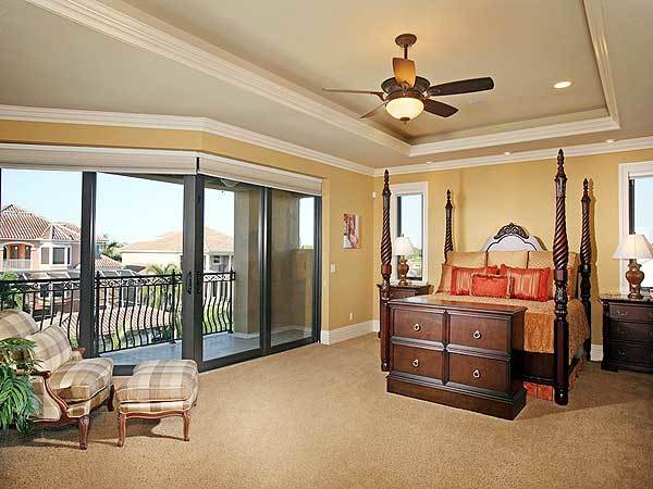 The spacious and bright primary bedroom has a alrge dark wooden four-poster bed that stands out against the beige walls, tray ceiling and beige carpeted flooring.