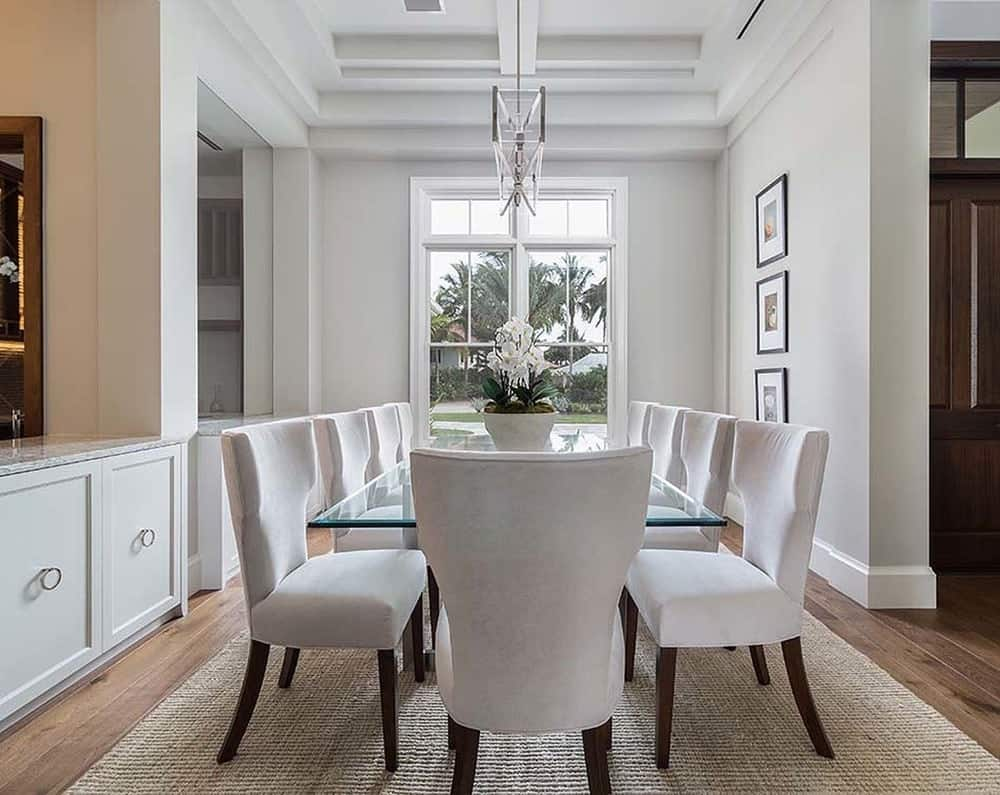 This formal dining room has a large glass-top dining table surrounded by light beige cushioned chairs to pair with the light tone of the walls and coffered ceiling.