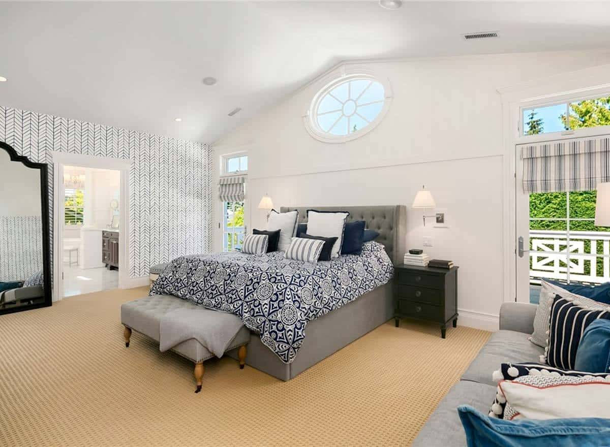 The tall cathedral ceiling of this bedroom is adorned with a circular transom window that brings in natural lights. This is augmented by the tall windows flanking the large gray bed that has a gray cushioned headboard complemented by dark wooden bedside drawers.