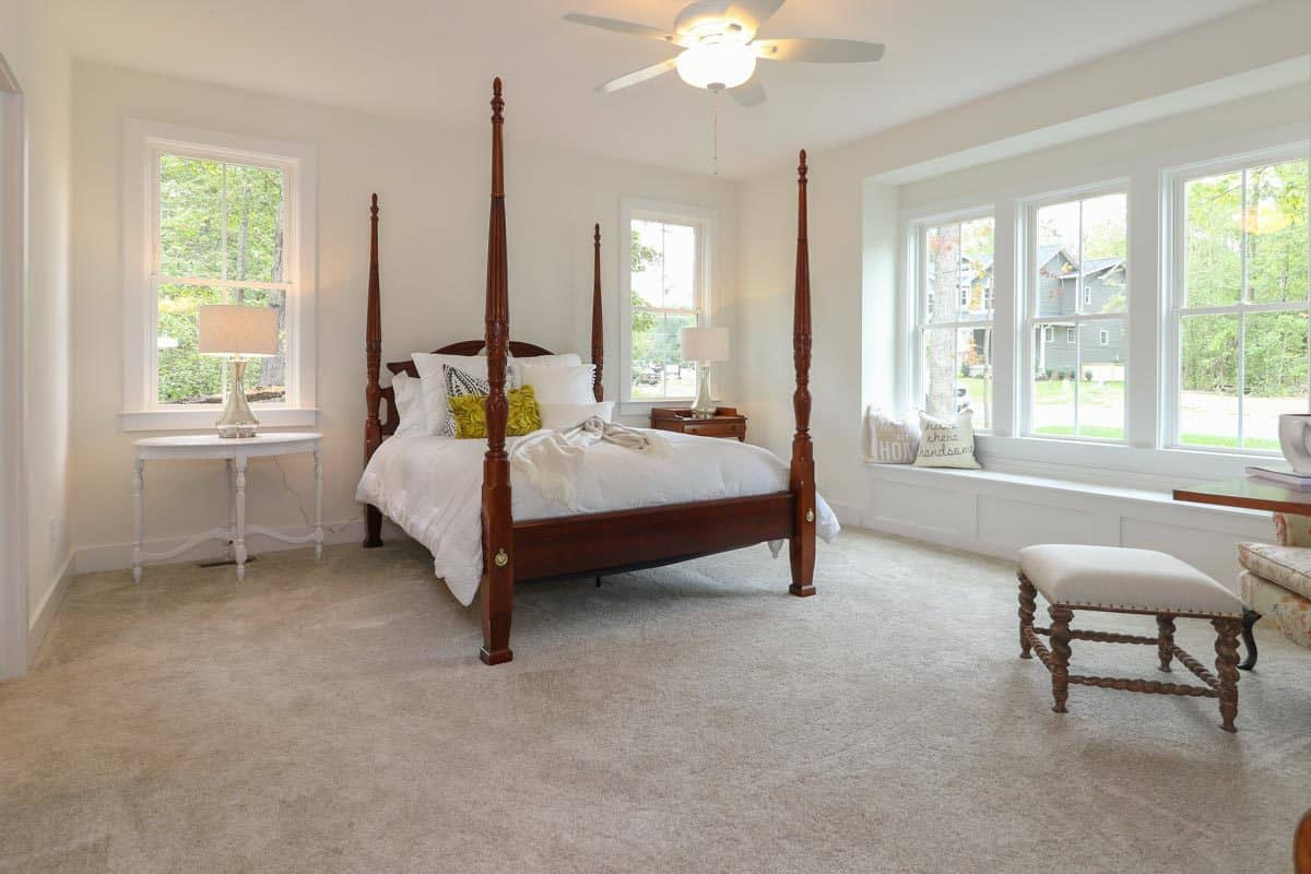 This bright and white spacious bedroom is dominated by the wooden four-poster bed that stands out against the brightness. This is augmented by the warm yellow light of the ceiling fan as well as the natural lights coming in from the window with a built-in seat below.