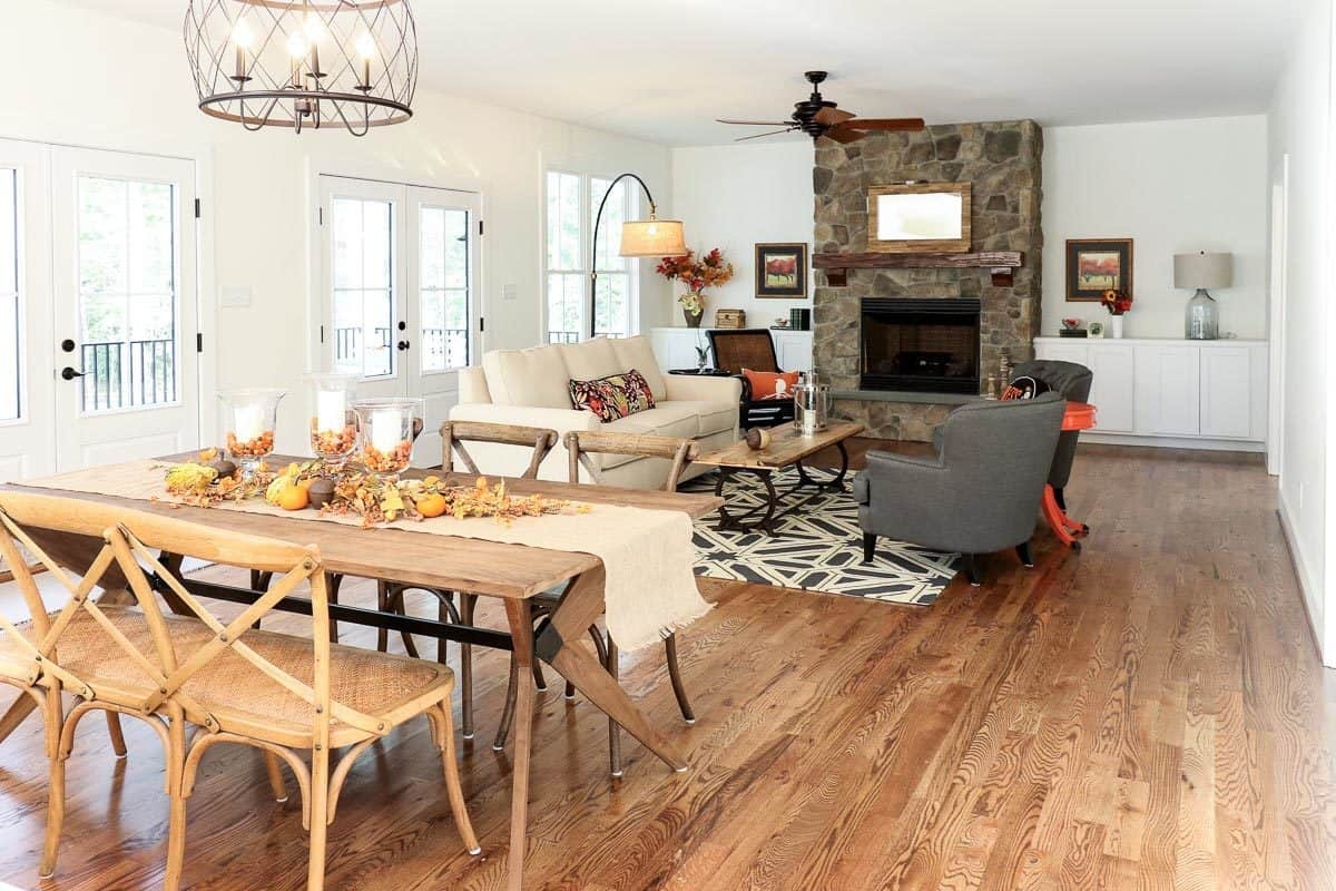 This living room is part of a great room that also houses the dining area beside it on the same charming hardwood flooring. This is complemented by the living room's large stone fireplace that stands out against the bright beige walls and ceiling.