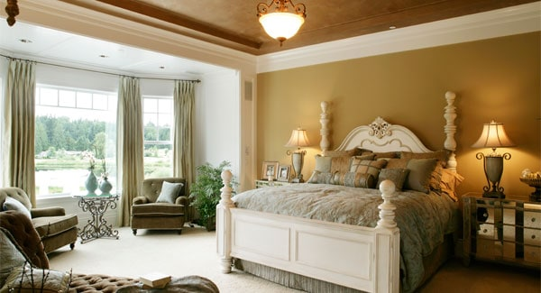 This bedroom has a brown tray ceiling that hangs a warm pendant light over the large wooden four-poster bed with a charming sitting area on the side by the windows.