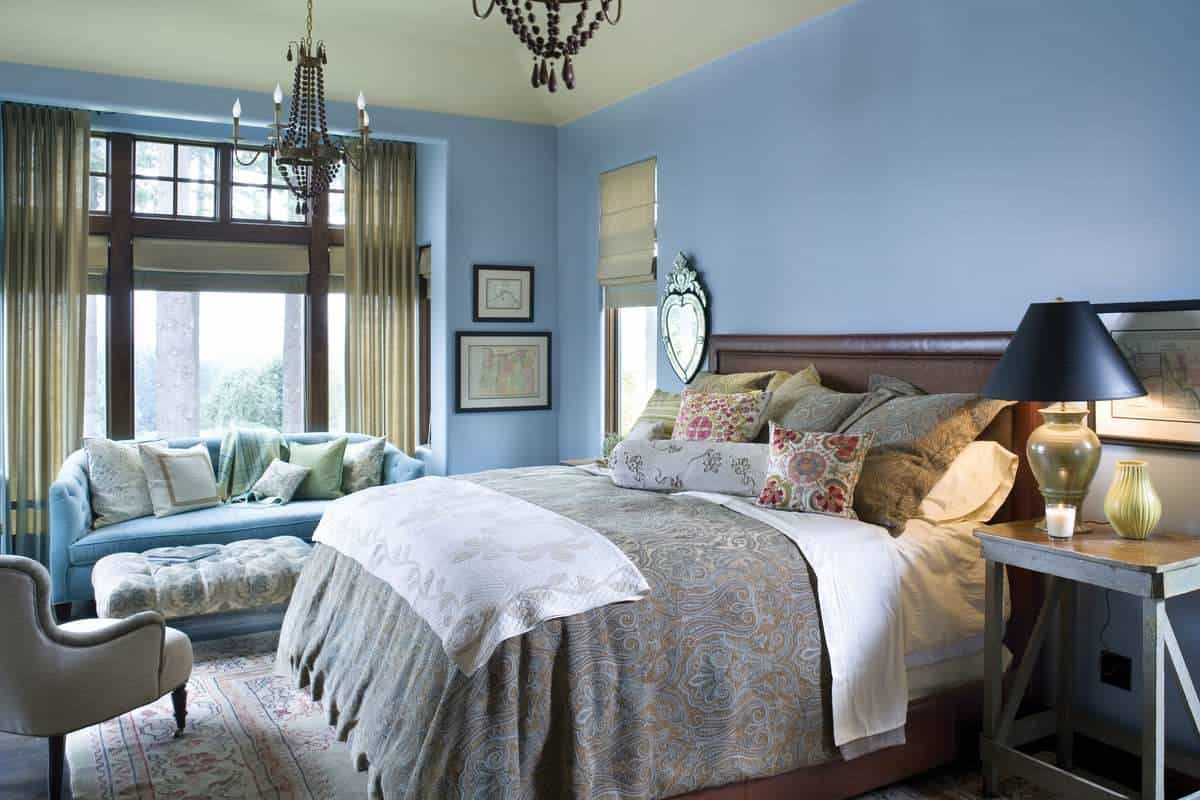 This bedroom has a nice blue-gray tone to its wall that complements the dark wooden headboard of the large bed topped with a decorative chandelier. On the side is a charming sofa by the window for a reading nook.