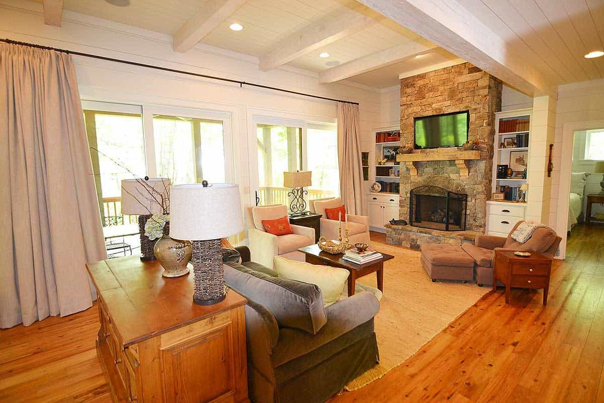 This is a homey living room with a large stone fireplace across from the cushioned sofa and its small wooden coffee table on a beige area rug that covers the hardwood flooring.