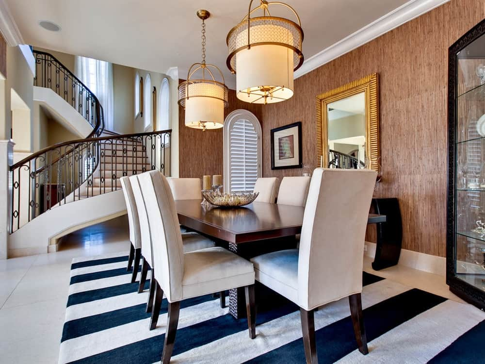 This formal dining room has a striped area rug that makes the light beige cushioned chairs stand out. The elegant dark wooden dining table is topped with a couple of drum pendant lights.