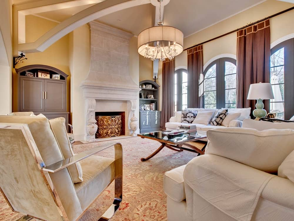 The large living room of the house has gorgeous beige walls, ceiling and patterned carpeting accented with a large stone fireplace that has elegant designs to match the comfortable sets of sofas.