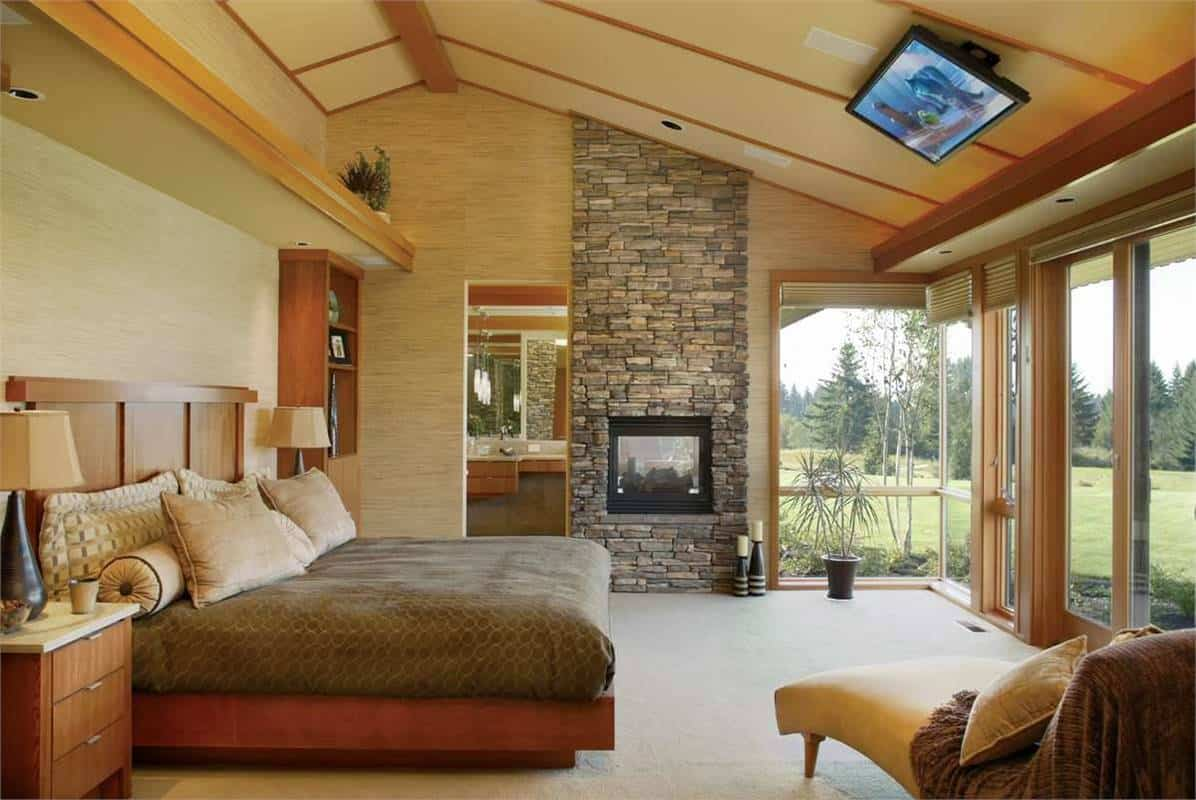 The large wooden platform bed stands out against the light gray floor and beige walls that extend to the beige arched ceiling with wooden exposed beams. The highlight of the bedroom are the glass walls and the large stone structure of the fireplace.