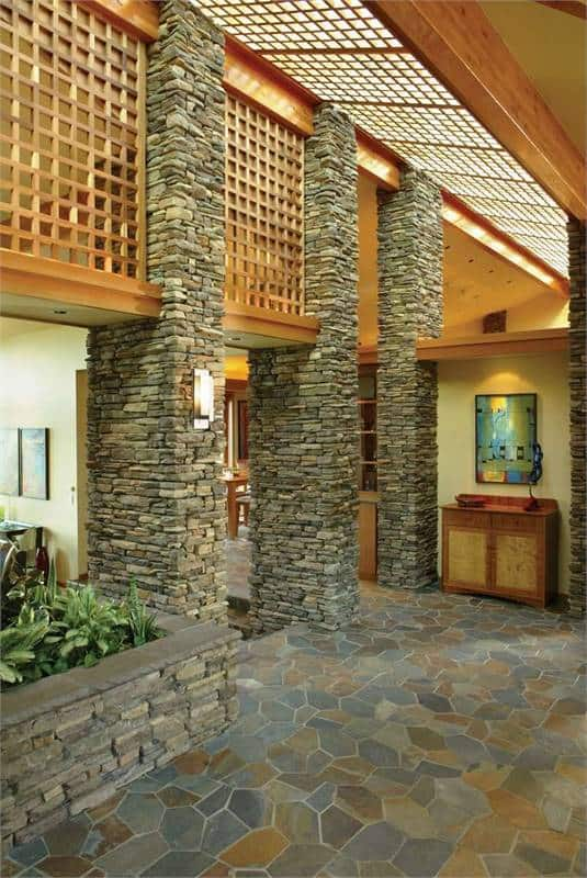 This lovely foyer has gorgeous textured stone pillars the are complemented by the wooden panels above. These rough textured stone pillars also match the stone flooring adorned with a planter on the side and a cabinet against the wall on the far side.