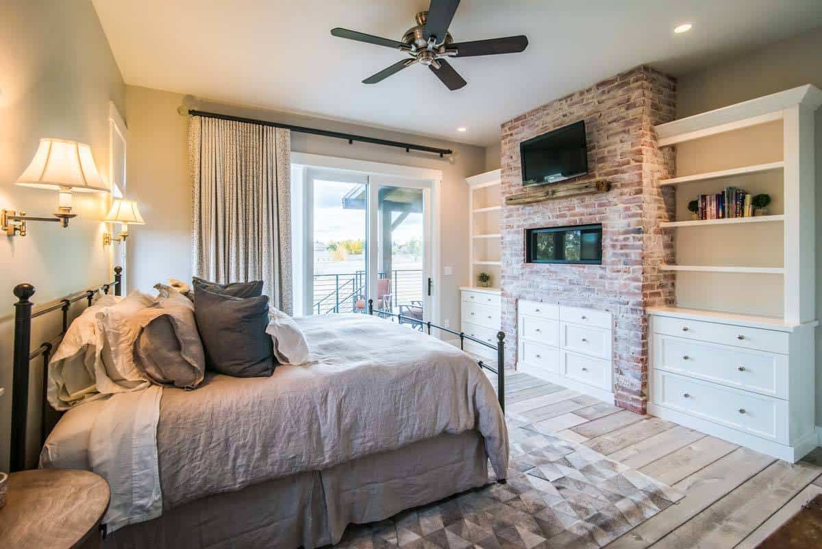 This is a homey and cozy bedroom with a large wrought iron bed on an area rug. Across from it is a large brick structure that houses a modern fireplace and a TV above.