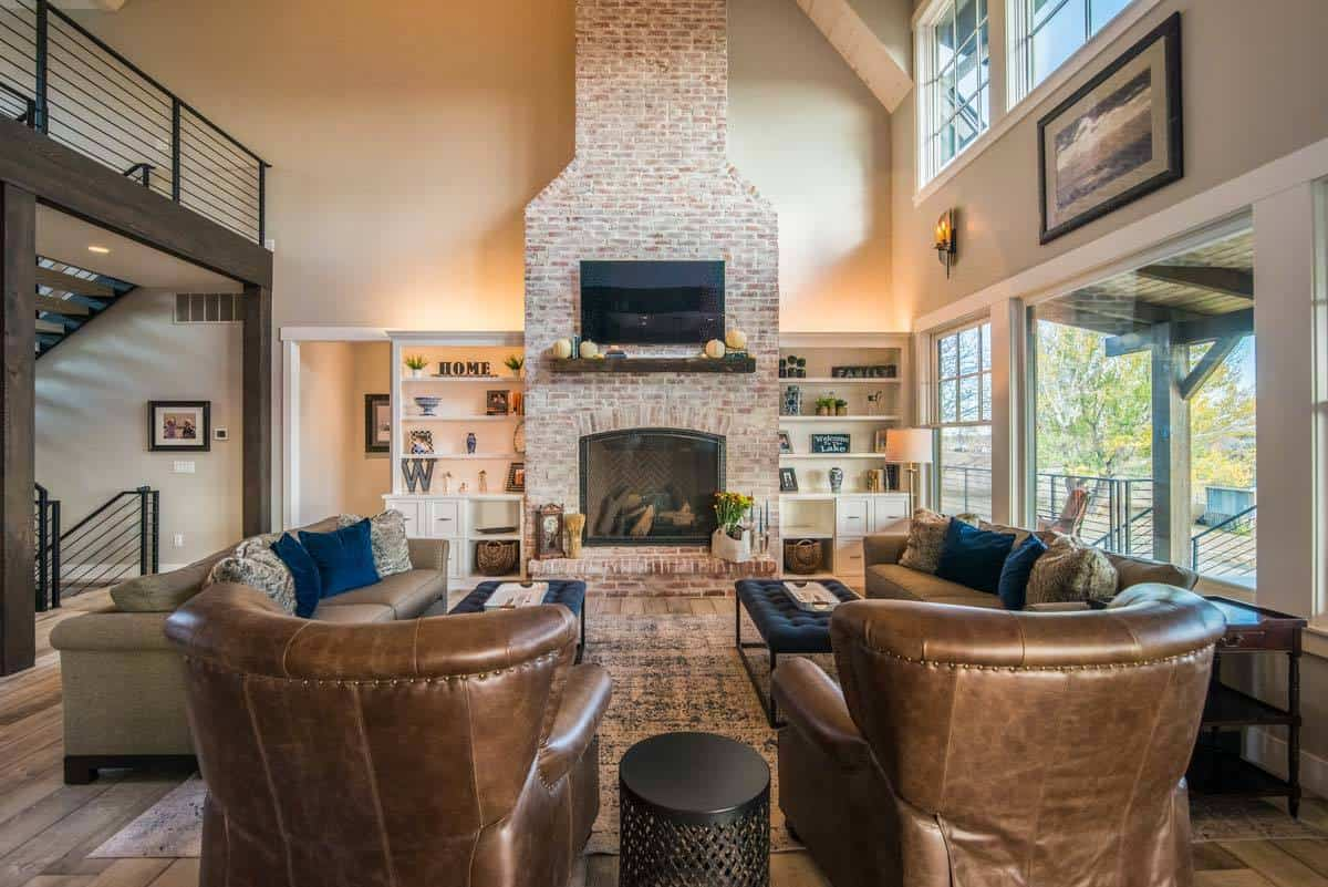 This charming living room has a tall ceiling paired with transom windows on one side and an indoor balcony on the other side. The living room is filled with gorgeous brown leather arm chairs and sofa facing the large stone structure of the fireplace.