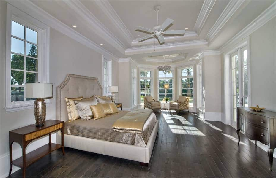 This is a spacious and airy bright primary bedroom. It has a dark hardwood flooring that contrasts the light beige walls and tray ceiling. On the far end is a sitting area by the tall windows.