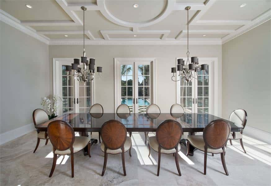This is a spacious formal dining room with a large rectangular dark wooden dining table that stands out against the bright beige walls and ceiling adorned with moldings and a couple of chandeliers.