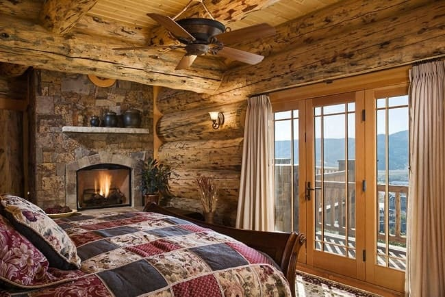 This gorgeous bedroom has charming log beam walls and ceiling that has a ceiling fan over the foot of the wooden sleigh bed. These are all warmed by the large stone fireplace on the side.