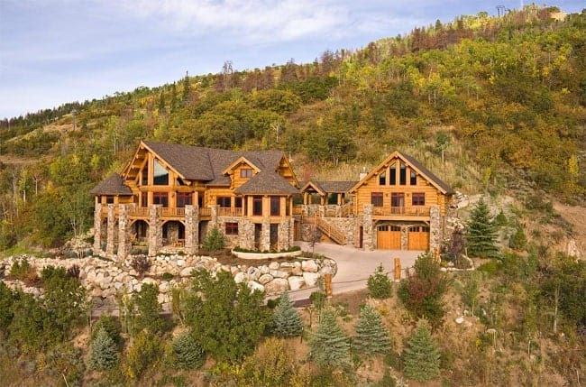 The gorgeous log house is complemented by the landscaping that has large decorative rocks lining the driveway as well as support the terraced lawns planted with shrubs, grass and small trees. These also match with the stone exteriors of the house as well as its stone pillars.