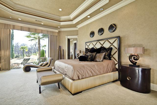 The primary bedroom features an elegant tufted platform bed and a chaise lounge by the full height glazing covered in beige drapes. The elegant tray ceiling matches well with the beige walls that contrast the bedside drawers.