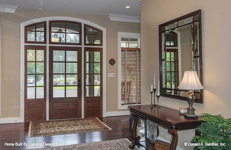 Upon entry of the house, you are welcomed by this foyer that has brown wooden French doors at the main door and brown wooden console table on the side. These elements match the hardwood flooring that is adorned with area rugs.