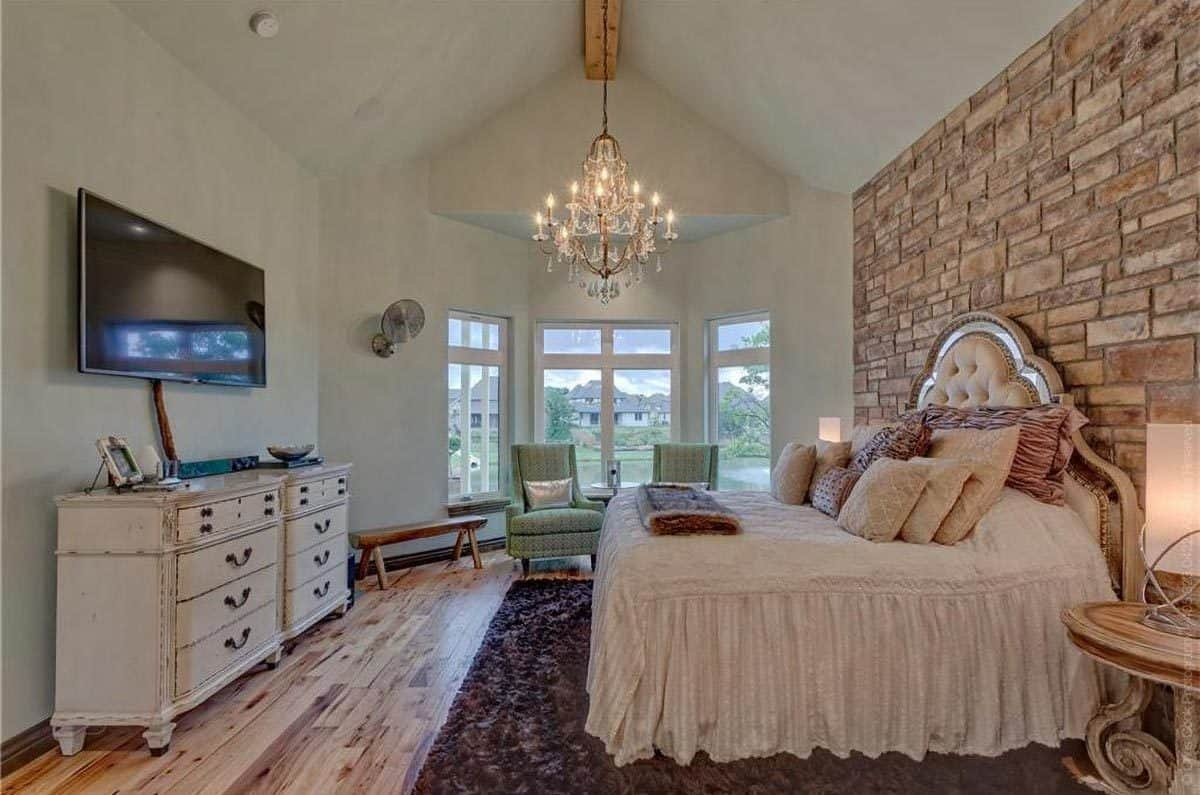 The beige cushioned headboard of the bed is complemented by the large stone brick wall behind it. The bedroom is topped with a cathedral ceiling that hangs a crystal chandelier over the foot of the bed.
