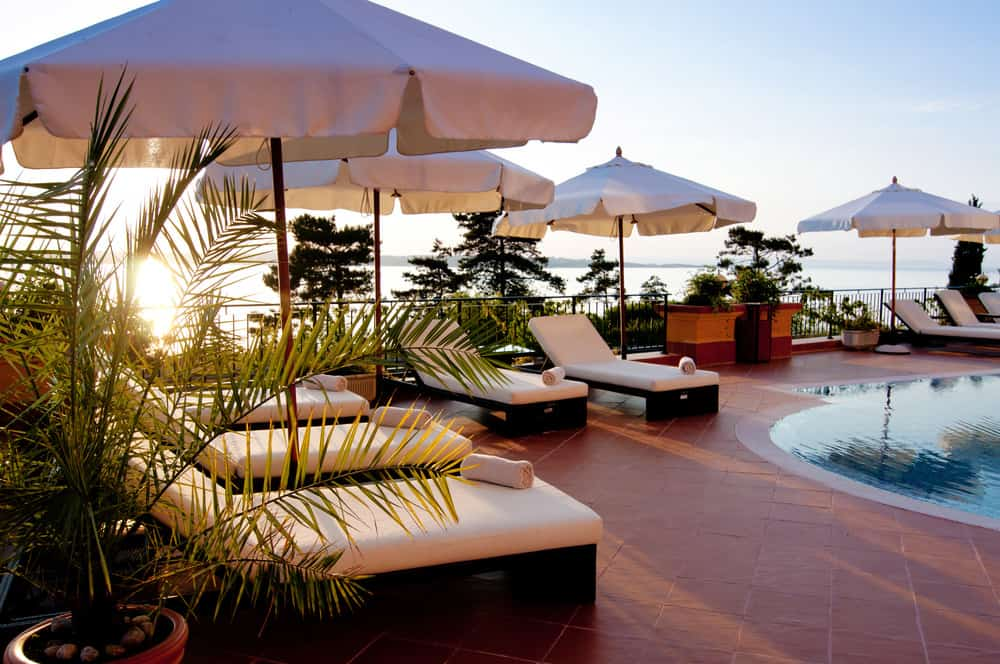 Luxury hotel pool deck with chaise lounge chairs