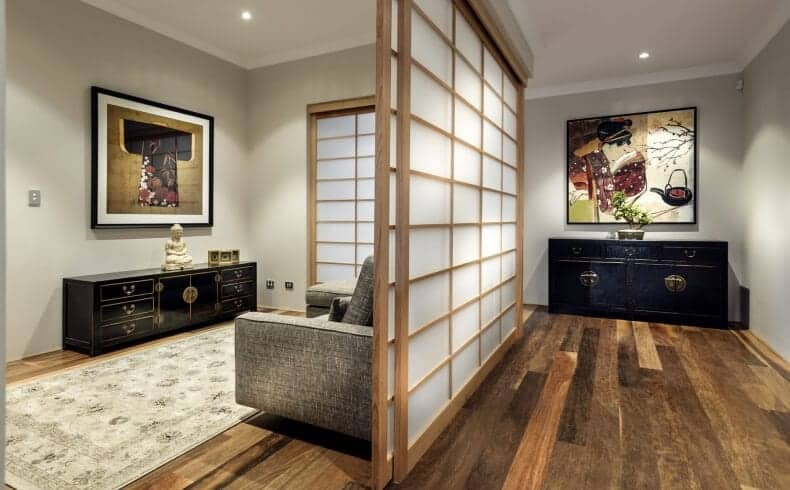 This Asian-style foyer has a warm welcome of hardwood flooring complemented by the dark cabinet that also serves as a console table on the far wall topped with a brilliant colorful old Japanese painting that colorfully contrasts the light gray walls and white ceiling.