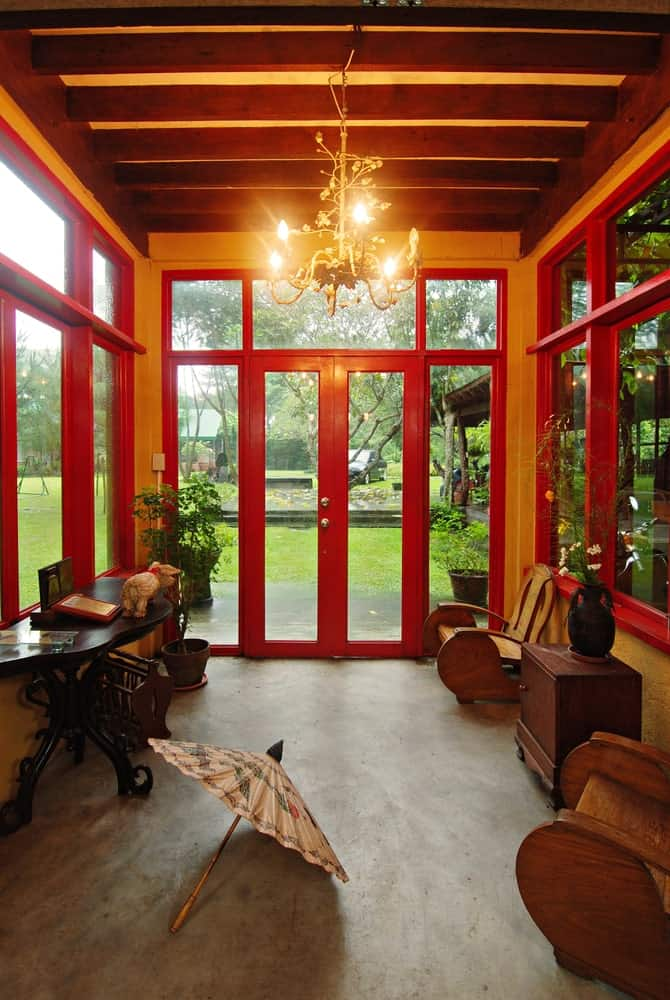 This brilliant foyer is surrounded by tall glass windows and door that has red wooden frames augmented by the yellow lights of the intricate chandelier hanging from the exposed wooden beams of the ceiling contrasted by the concrete flooring.