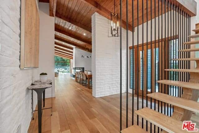 This is a view of the foyer as seen from the vantage point of the wooden stairs with wrought iron railings. You can see the main door which is filled with glass panels that bring in natural lights to the white textured walls and the wooden shed ceiling matching with the hardwood flooring.