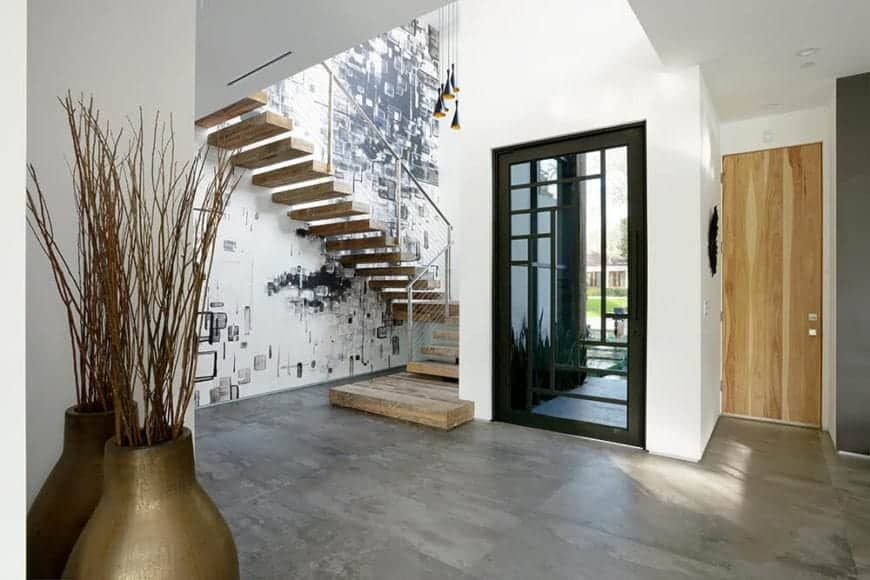 The main door has a glass panel in the middle adorned with black frames that has an oriental design matching the simple interior of the foyer. The floor is made of gray concrete and the white walls are filled with abstract art that makes the golden vases stand out.