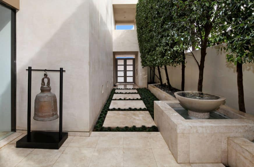 The charming zen foyer has a beige marble walkway that matches with the plant box of the trees lining the walls and the inlay of the zen fountain on the side across from the decorative antique bell supported by a plain black rack that contrasts the flooring and walls.