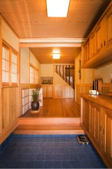 This lovely Asian-style foyer has a Japanese sensibility and charm to it. Upon entry, you will set foot on a brilliant blue-tiled floor. You will have to remove your shoes before you can move on to the hardwood flooring of the rest of the home that matches with the cabinets, ceiling and doors.