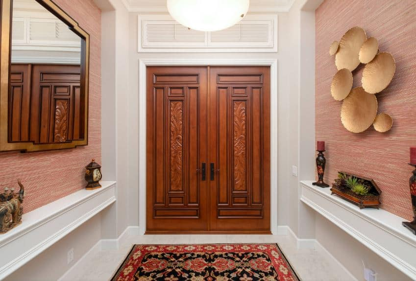 This elegant Asian-style foyer has wooden double doors for its main entry. This door is adorned with carvings that bring character to the simple walls of the foyer that has built-in shelves filled with small decors.