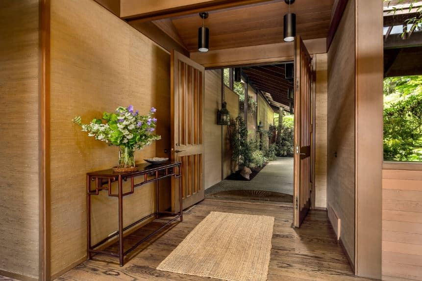 The small garden just outside of the main entry leads to this small foyer with its wooden double doors matching the wooden console table that has a distinct oriental design. It also matches with the wooden ceiling that hangs two <a class=