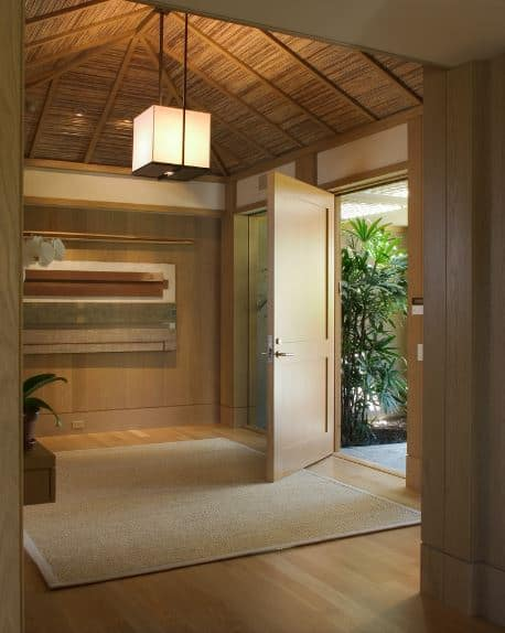 The charming wooden ceiling of this Asian-style foyer gives a slight tropical feel to the wooden walls and main door that matches with the hardwood flooring topped with a light brown woven area rug bathed with natural lights from the open door.
