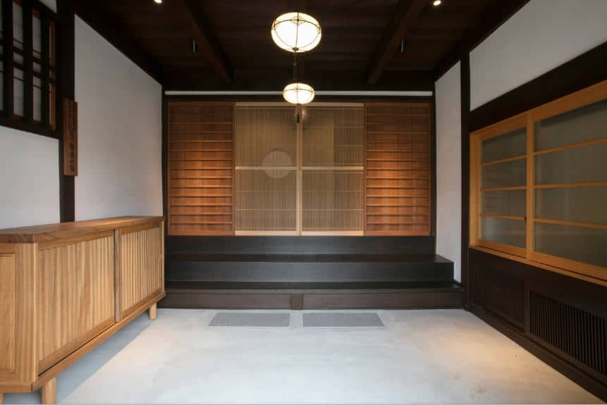 This is a simple Japanese-style style foyer with a light gray concrete floor with a small wooden cabinet for the shoes. After changing into indoor footwear, you can climb up the black stairs to the wooden sliding door that give access to the rest of the home.