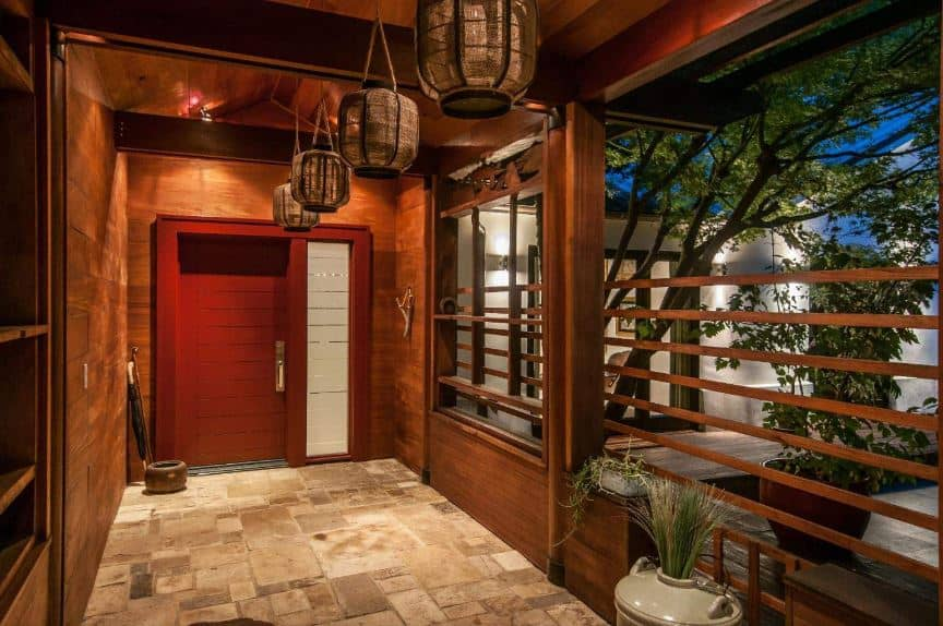 This is a hallway-like Asian-style foyer with a wooden main door that has a red hue matching the redwood walls and wooden ceiling with exposed wooden beams that support the pendant lights with decorative woven wicker lantern hoods.