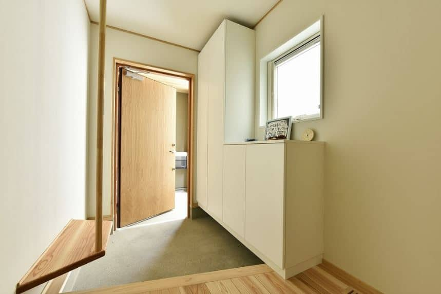 This is a simple and small Asian-style foyer with a built-in white wooden cabinet for the shoes blending in with the white walls. The hardwood flooring matches with the wooden door and the built-in small bench for changing footwear.