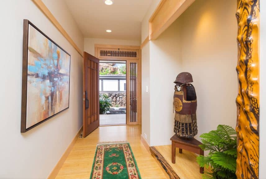 The wooden main door that has an elegant oriental design leads into this hallway-like Asian-style foyer that has light hardwood flooring topped with a green patterned area rug. The white walls are adorned with a colorful painting on the left and a Japanese armor on the right.