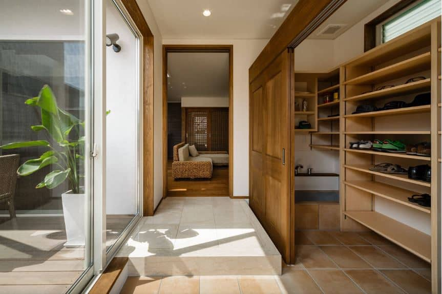 This is a small Asian-style foyer with beige tiles leading to a small closet on the right that has wooden shelves for the shoes and there is even a small faucet on the corner. After changing footwear, you can enter the rest of the home that has hardwood flooring through a small white landing.
